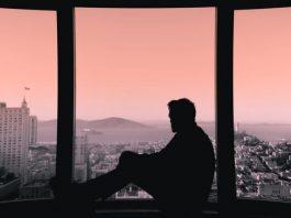 Man staart uit het raam